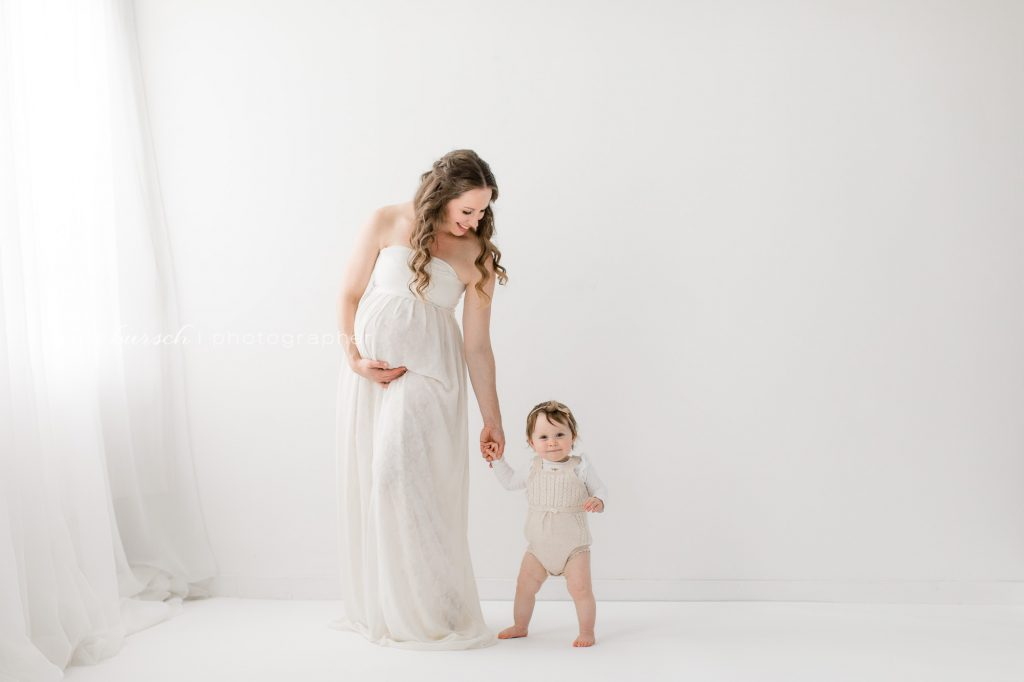 pregnant mom holding toddlers hand white gown