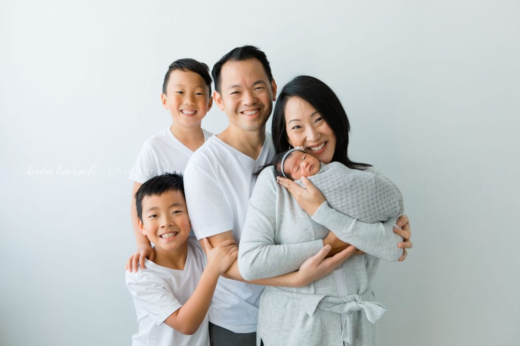 asian family looking at camera smiling with newborn