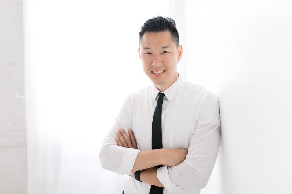 asian man professional on white background looking at camera smiling